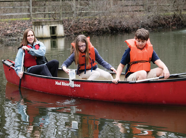 Fifth graders Reagan Schriver (C) and Colin Helbling (R) collect pond samples with science teacher Heather Capezzuti (L).