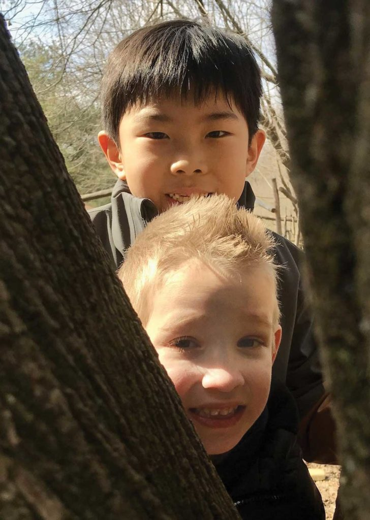 two young students peek between trees