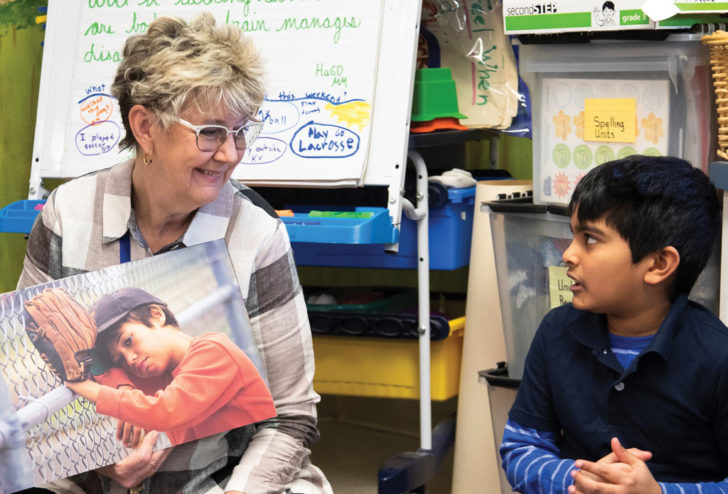 Teacher reads to young student