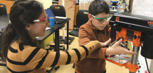 Teacher helps student with drill press