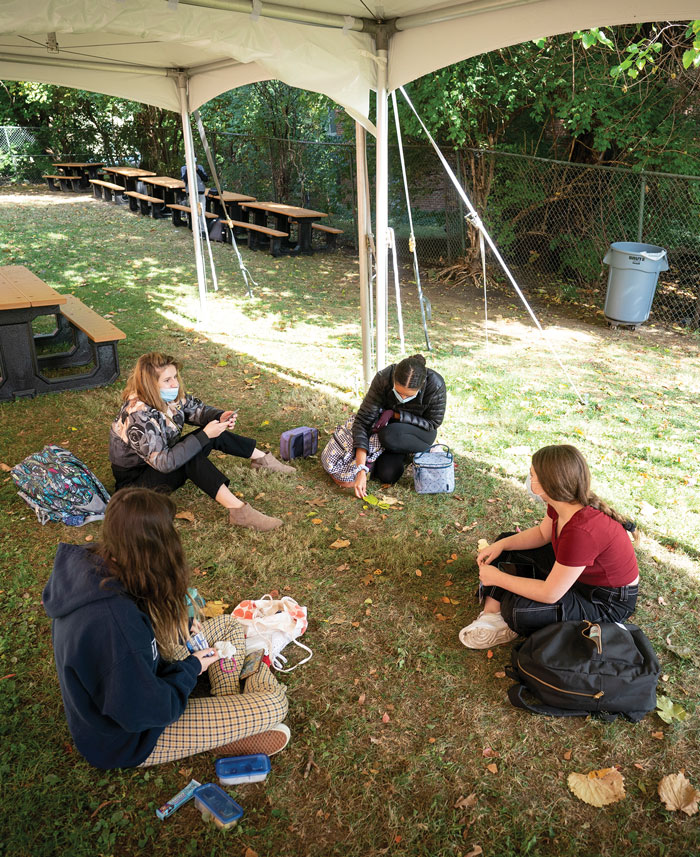 students gather under tent in outdoor space